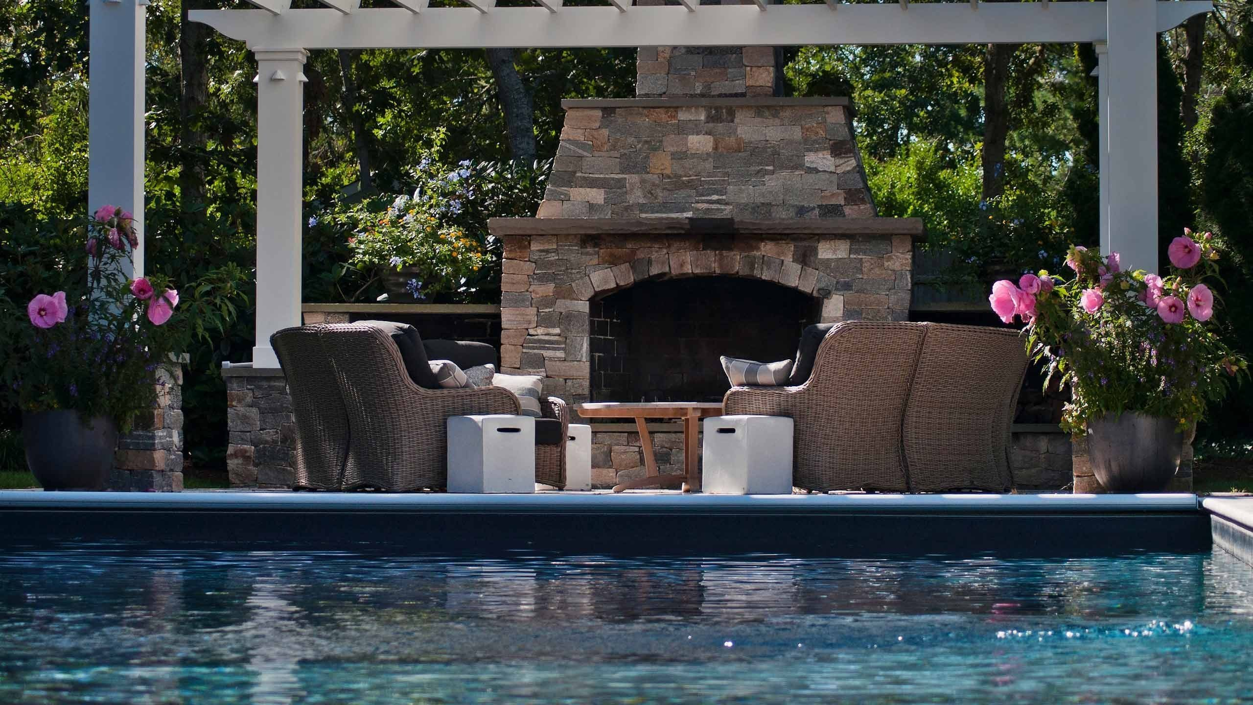 Outdoor fireplace in patio next to custom swimming pool